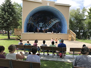 Band playing in old fashioned band clam shell. People in foreground sitting listening to the music on park benches.