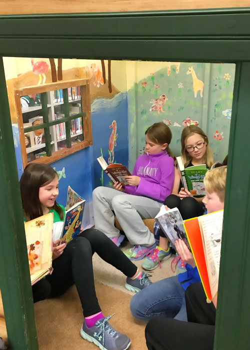 Children reading together in the playhouse at the Paynesville library.