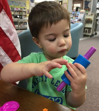 Photo of toddler boy with playdoh and rolling pin